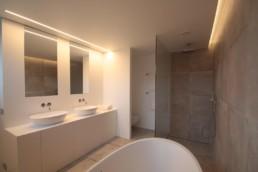 foto van een moderne badkamer getrokken van achter het vrijstaande bad. Recht vooruit rechts zie je de inloopdouche met regendouchekop, links een toilet achter een muur, aan de muur handdoekrekken en rechts lavabomeubel met spiegels boven