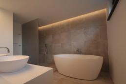 foto met achteraan in de hoek een inloop douche, verder staat er rechts een vrijstaand, ovaal bad. tegen de muur van waaruit de foto werd genomen staat het lavabomeubel met twee vrijstaande lavabo's op de kast