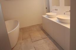 foto van vrijstaand bad in de linkerhoek en een lavabomeubel met onderaan kasten en bovenop de kast 2 vrijstaande lavabo's, boven elke lavabo hangt een afzonderlijke spiegel