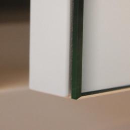 detailfoto van de afwerking van deur met een spiegel van een spiegelkast boven de lavabo