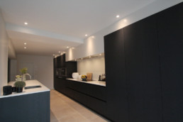 Moderne keuken met keukenkastjes in een zwarte afwerking. het keukenblad is wit. boven de keukenkasten zijn spots verwerkt in het plafond