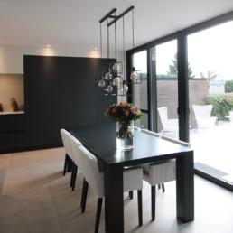 foto van de eettafel met daarboven een moderne luster. achter de tafel is een grote schuifdeur die toegang biedt naar de tuin