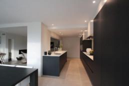 foto van de keuken met een zwarte afwerking. boven de keukenkasten zijn in het plafond spots verwerkt
