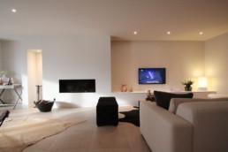 foto van een moderne living. openhaard werd in de muur gewerkt. Televisie hangt aan de muur. onder de televisie staat een op maat gemaakte lage kast. In het planfond zitten spotjes verwerkt en op de vloer werden grootformaat keramische tegels in een beige kleur gebruikt.