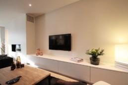 foto van een moderne living. In de living staat een op maat gemaakt TV-kast. Televisie hangt aan de muur. In het plafond zijn spots verwerkt