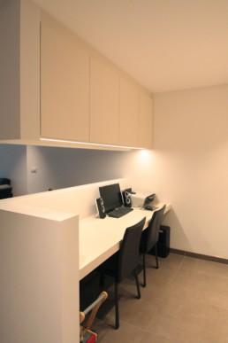 foto van het bureau met boven het werkblad zwevende kasten gemonteerd aan het plafond en tegen de muur. de vloer bestaat uit grijze keramische grootformaattegels