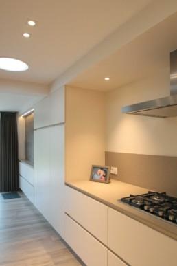 foto van de keuken met lichttunnel in het plafond. er werd gekozen voor een gasfornuis in inox, witte kasten en een beige werkblad en spatwand die in elkaar over gaan
