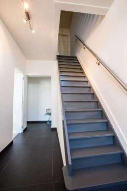 foto van een moderne hal. Grijs geverfde trap, witte muren en donker grijze tegels op de vloer. de trapleuning tegen de muur is in aluminium