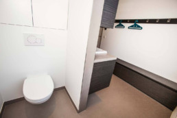foto van een moderne badkamer, grijze tegels op de vloer, bruine kasten en kapstokken aan de muur