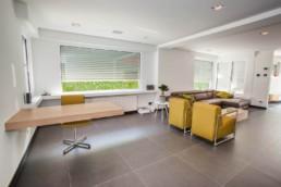 foto van een living, grote tegels op de vloer, witte muren, gele retro zetels en verder moderne meubels en strakke lijnen