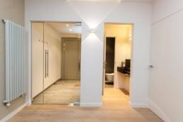 foto van een moderne witte inkomhal, met legklaar parket op de vloer, glazen deur richting de voordeur en doorgang richting een gastentoilet. wandverlichting en een moderne centrale verwarming tegen de muur