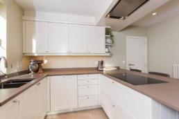 foto van de keuken met witte kastjes, beige tegels op de vloer en bruin-grijs werkblad