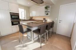 totaalzicht van keuken met witte kastjes, bruin-grijs werkblad en beige grote tegels op de vloer