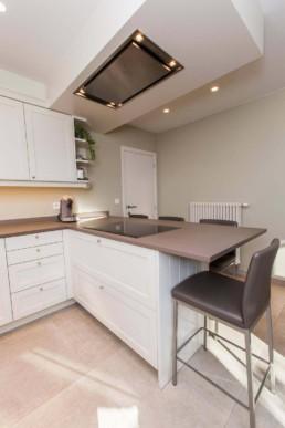 foto van keuken met ontbijtbar. Keuken met witte kastjes, beige tegels op de vloer en bruin-grijs werkblad