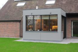 Moderne aanbouw met Trespa panelen in neutraal grijs, aluminium ramen en een schuifdeur richting de tuin. Natuurprijze terrastegels op het terras in de tuin.