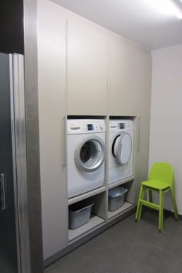 foto van de berging. Foto van de ingemaakte kasten waarin de wasmachine en droogkast ingebouwd zijn