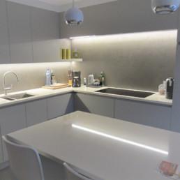 foto van de keuken in de aanbouw. De algemene kleur van de keuken is neutraal grijs met een wit werkblad in composiet.