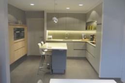 Totaaloverzicht van de keuken, rechts zijn er keukenkasten, het fornuis. Centraal een bartafel en links een ingebouwde kast met ingebouwde oven
